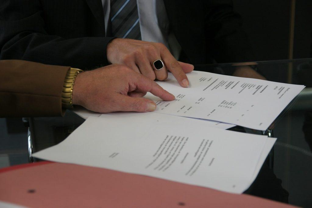 Bild von zwei Personen, die sich eine Vertragsseite ansehen.