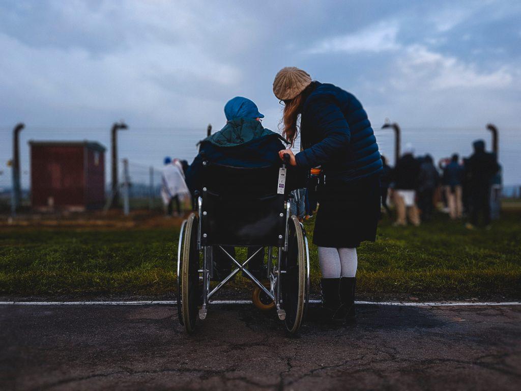 Frau, die in der Nähe einer Person im Rollstuhl in der Nähe einer grünen Wiese steht.