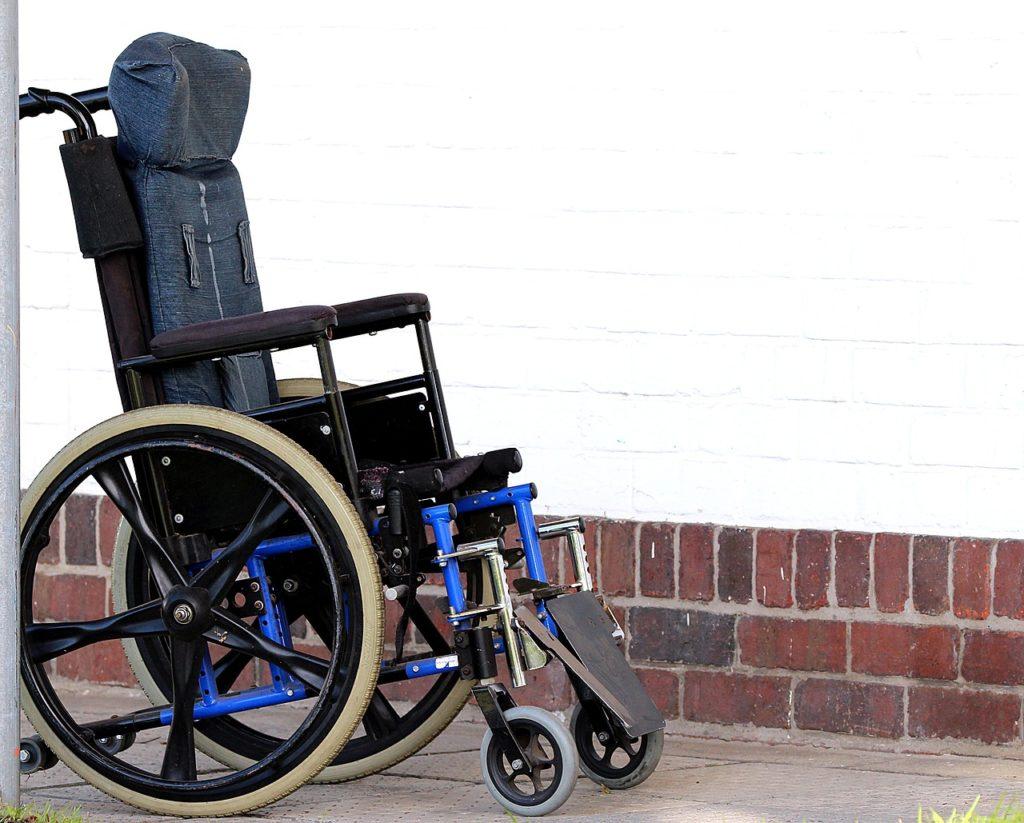 Nahaufnahme eines Rollstuhls in der Nähe einer Wand